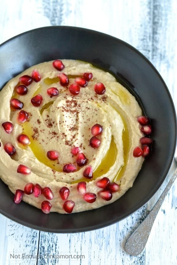 overhead shot of homemade easy hummus drizzled with olive oil and sprinkled with pomegranate seeds and sumac