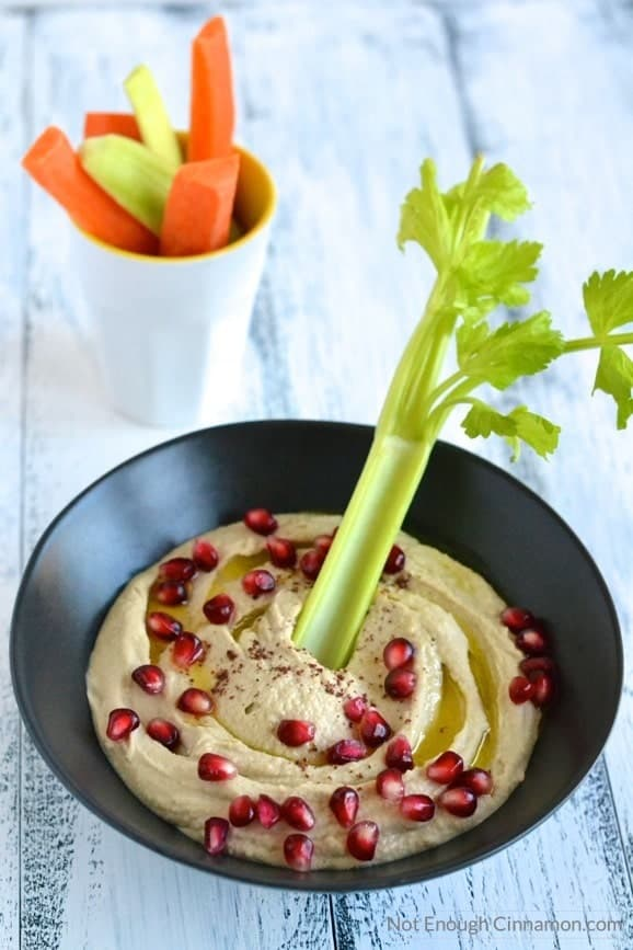 creamy and smooth homemade hummus served in a black bowl sprinkled with sumac and pomegranate arils, with some veggie sticks on the side - easy hummus recipe