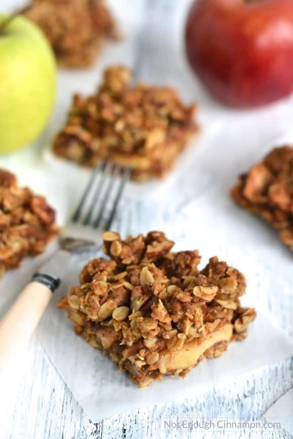 side view of healthy Apple Pie Oatmeal Bars arranged on a rustic white table with a fork and red and green apples in the background