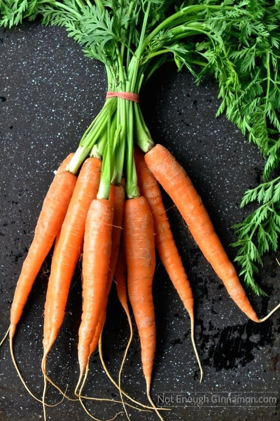 a bunch of fresh carrots on a dark tabletop ready to be roasted