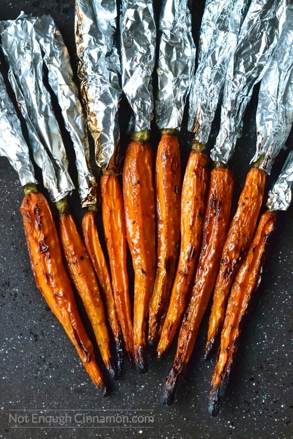balsamic roasted carrots fresh out of the oven with aluminum foil still wrapped around the greens