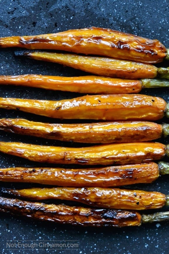 caramelized balsamic roasted carrots lined up horizontally on a dark tabletop