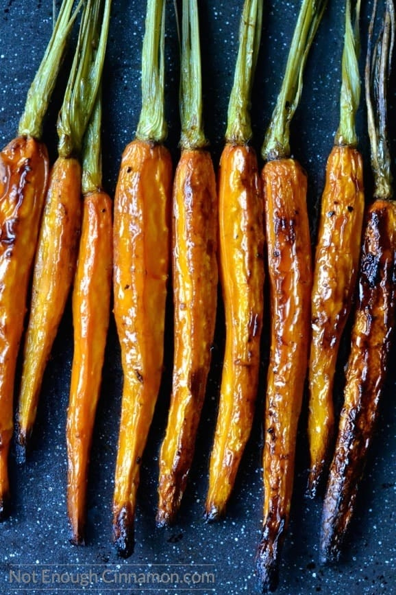 lightly charred, whole balsamic roasted carrots lined up next to each other on a dark tabletop