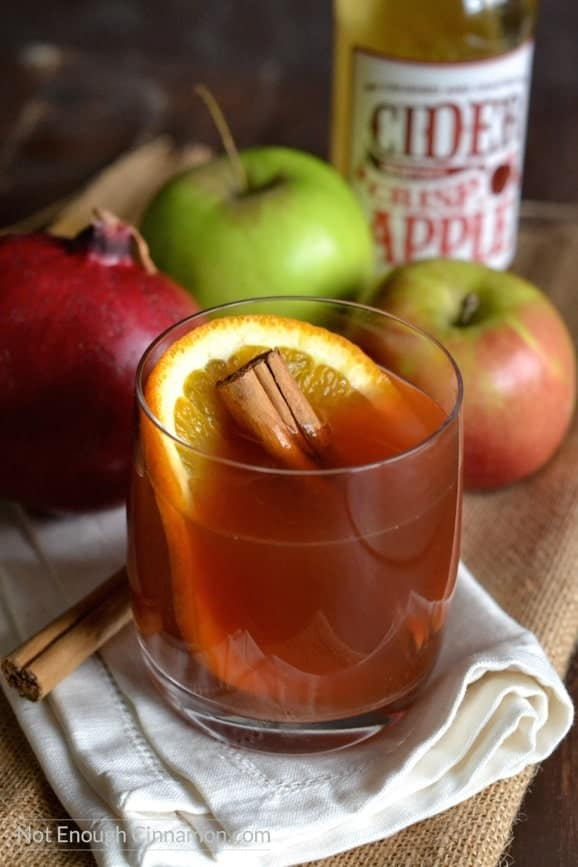 side view of a glass of pomegranate spiced apple cider with with an orange slice and cinnamon stick in it and apples in the background