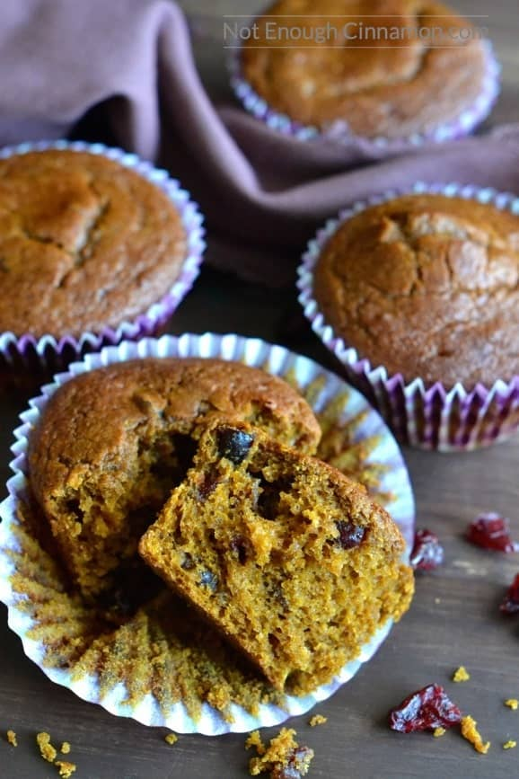 a healthy pumpkin cranberry muffin torn into two pieces to reveal the fluffy and moist inside