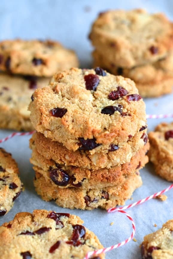Healthy Cranberry and Macadamia studded Paleo Cookies stacked on top of each other on parchment paper