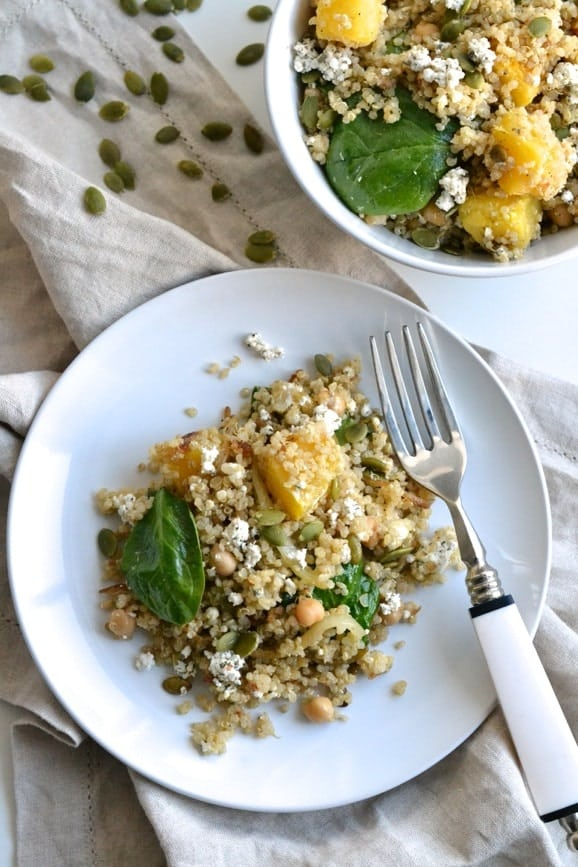 overhead shot of a plate of quinoa salad with roasted acorn squash, spinach chickpeas and crumbled goat cheese