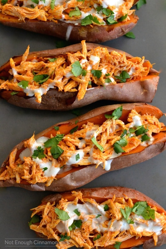 overhead shot of four baked sweet potatoes loaded with buffalo shredded chicken and drizzled with skinny blue cheese sauce