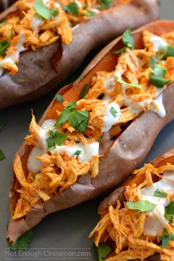 close-up of a baked sweet potatoes loaded with shredded buffalo chicken and drizzled with skinny blue cheese sauce!