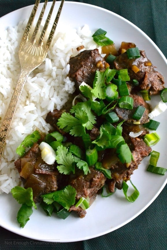 close-up of a plate of slow cooker ginger beef served with a side of rice and some chopped cilantro