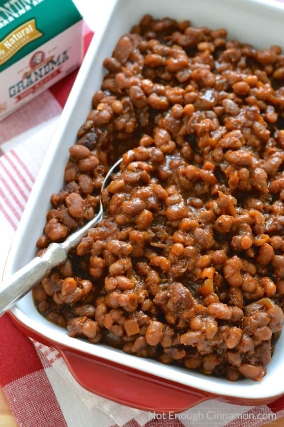 Homemade slow cooker baked beans with molasses and bacon in a red casserole dish