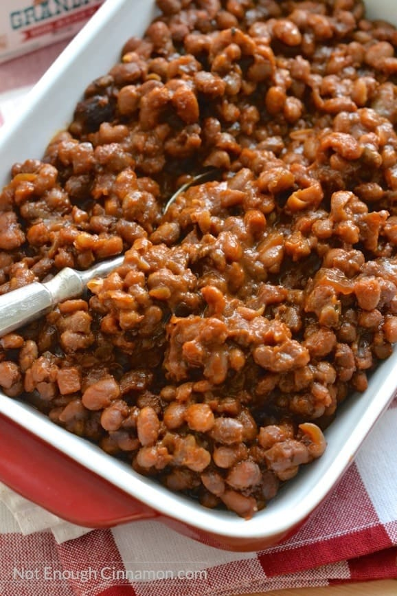 close-up on a casserole with homemade slow cooker baked beans with a spoon on the side