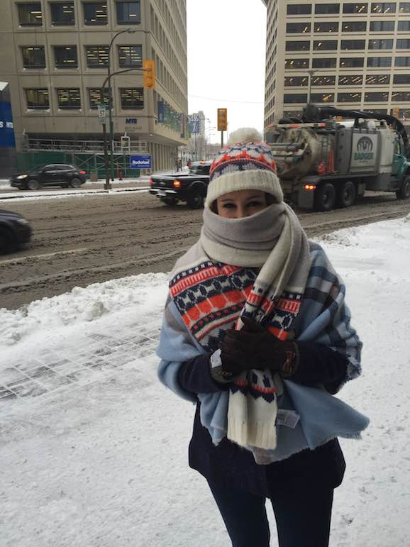a woman standing on a snow-covered sidewalk outside of Winnipeg station wrapped in several shawls