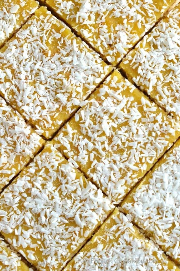 a freshly cut batch of Paleo Coconut Bars with orange curd and shredded coconut on top