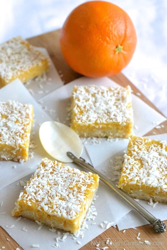 Paleo Orange Curd Coconut Bars arranged on squares of white parchment paper with an orange in the background