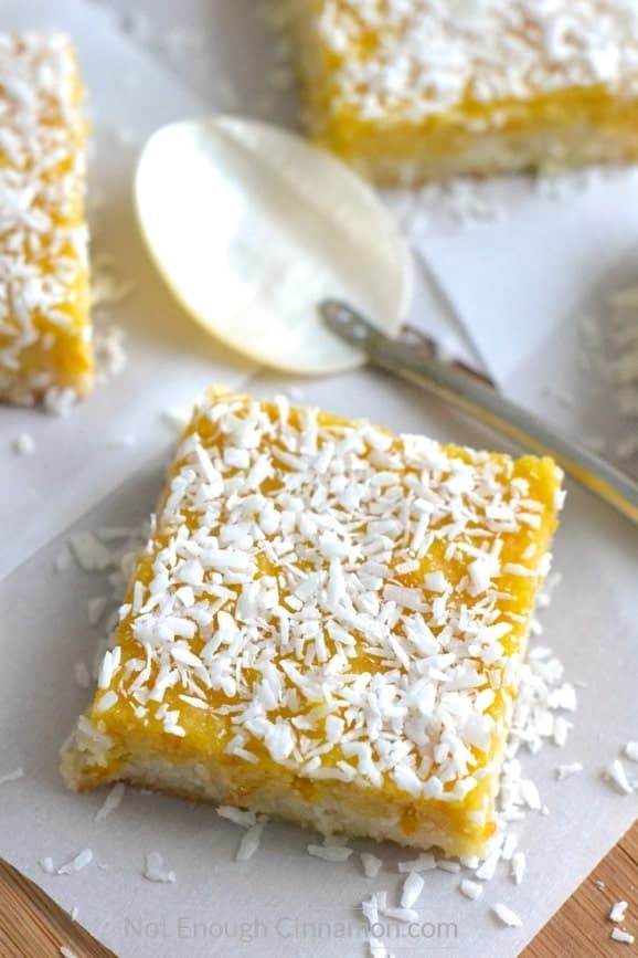 Paleo Coconut Bars with Orange Curd arranged on parchment paper with shredded coconut sprinkled on top