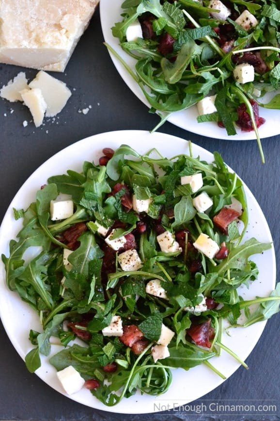 two plates of Blood Orange, Mozzarella and Arugula Salad with a wedge of parmesan cheese on the side