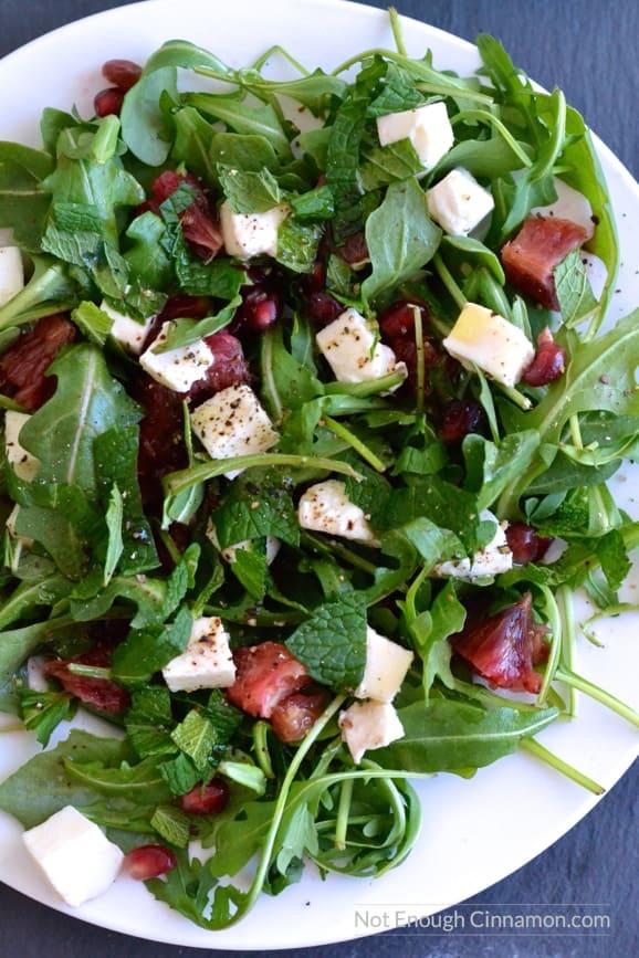 overhead shot of Blood Orange, Mozzarella and Arugula Salad with lemon dressing on a white plate