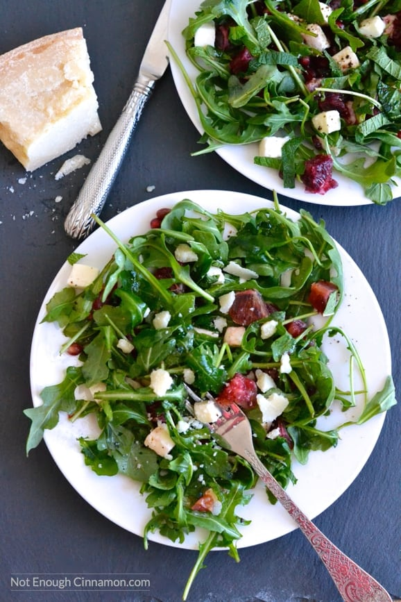 two plates of Blood Orange, Mozzarella and Arugula Salad with pomegranate arils and mint leaves