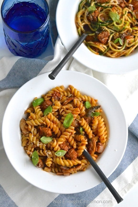 two bowls of Italian Sausage Pasta - one with fusilli noodles, one with zoodles