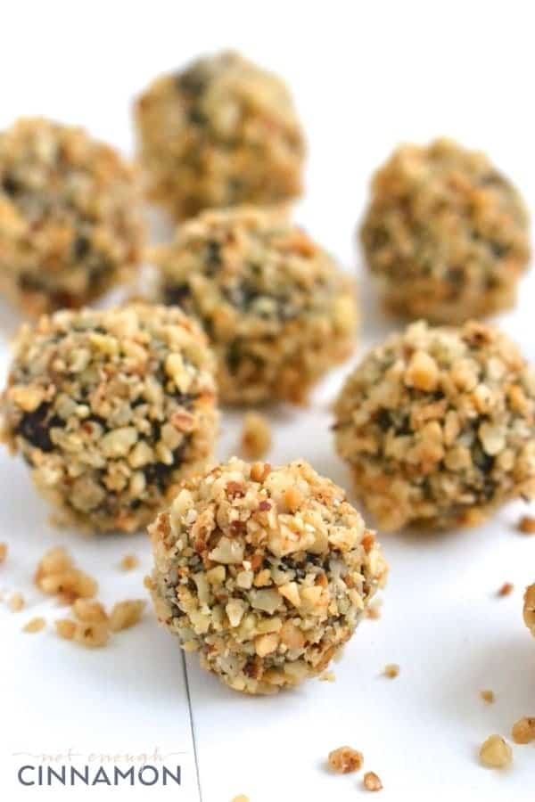 Ferrero Rocher Copycat Healthy Energy Balls with chocolate and hazelnuts on a white tabletop