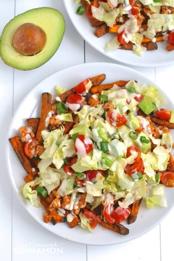 overhead shot of Clean Eating Turkey Taco Loaded Baked Sweet Potato Fries in a white plate with half an avocado on the side