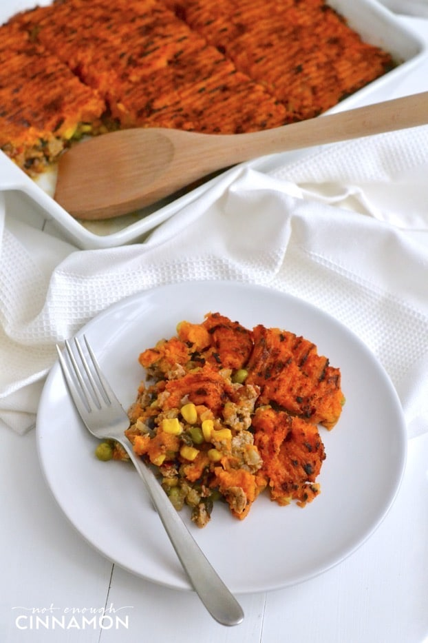 a serving of paleo sweet potato shepherd's pie on a white plate with a casserole dish in the background