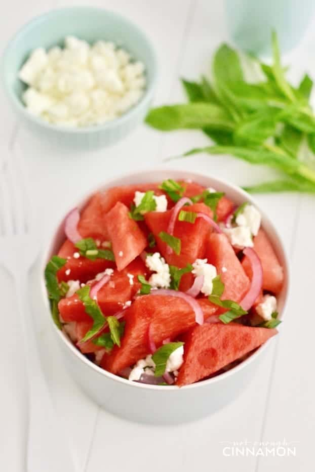 a bowl of watermelon salad with feta and mint with some fresh mint and a side dish of crumbled feta in the background