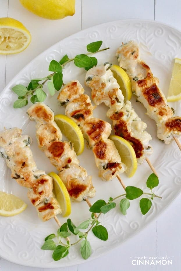 overhead shot of Greek Lemon Chicken Skewers on a white serving plate with lemons in the background