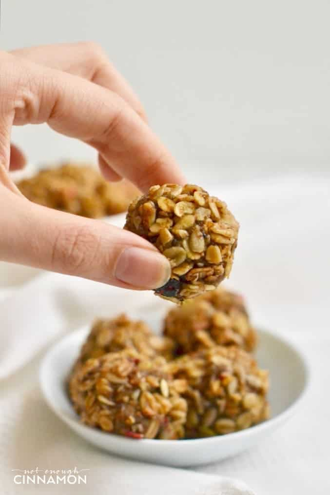 a hand holding a Healthy No Bake Granola Bite with a small plate of granola bites in the background