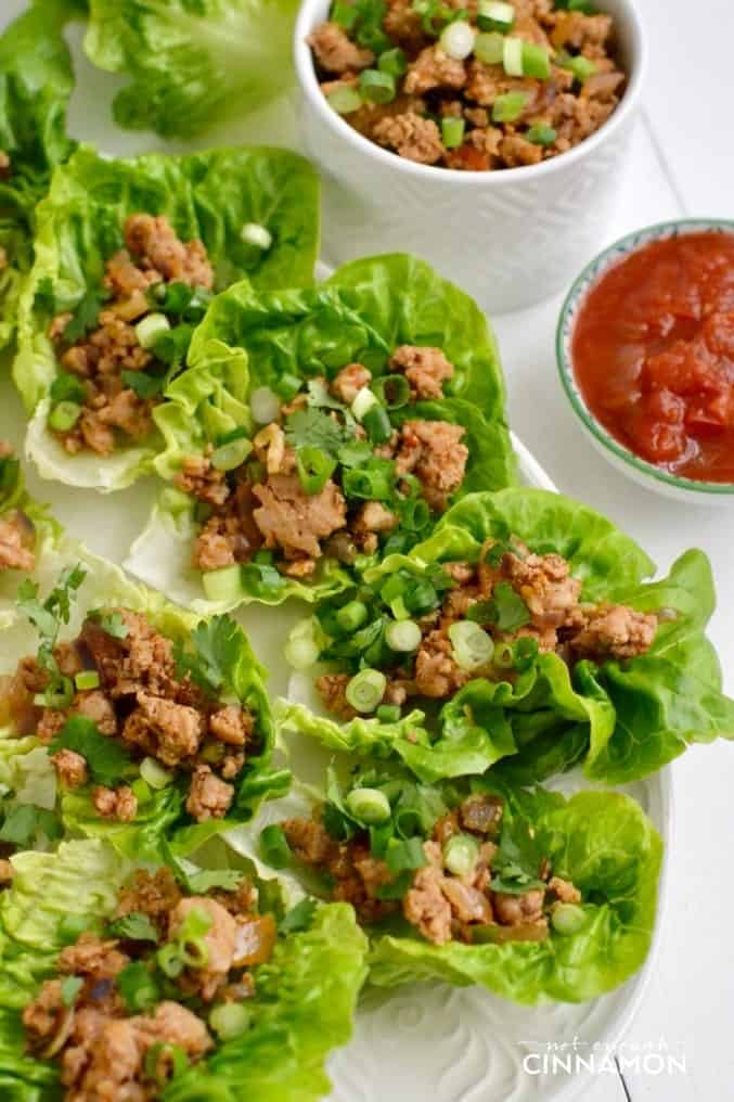 overhead shot of turkey taco lettuce wraps served on a big platter with small side dishes of ground turkey and salsa on the side