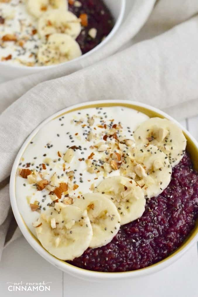 close-up of healthy berry quinoa breakfast bowl topped with Greek yogurt, banana slices and chia seeds