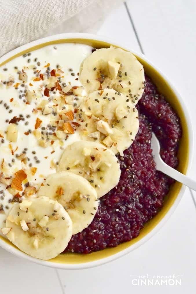 close up of healthy berry quinoa breakfast bowl topped with Greek Yogurt, banana slices and chia seeds