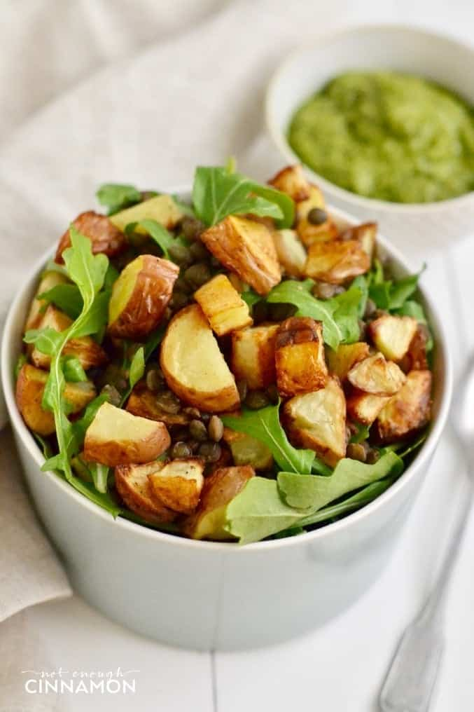 a bowl of roasted potato and lentil salad with arugula served with a side dish of homemade walnut pesto dressing