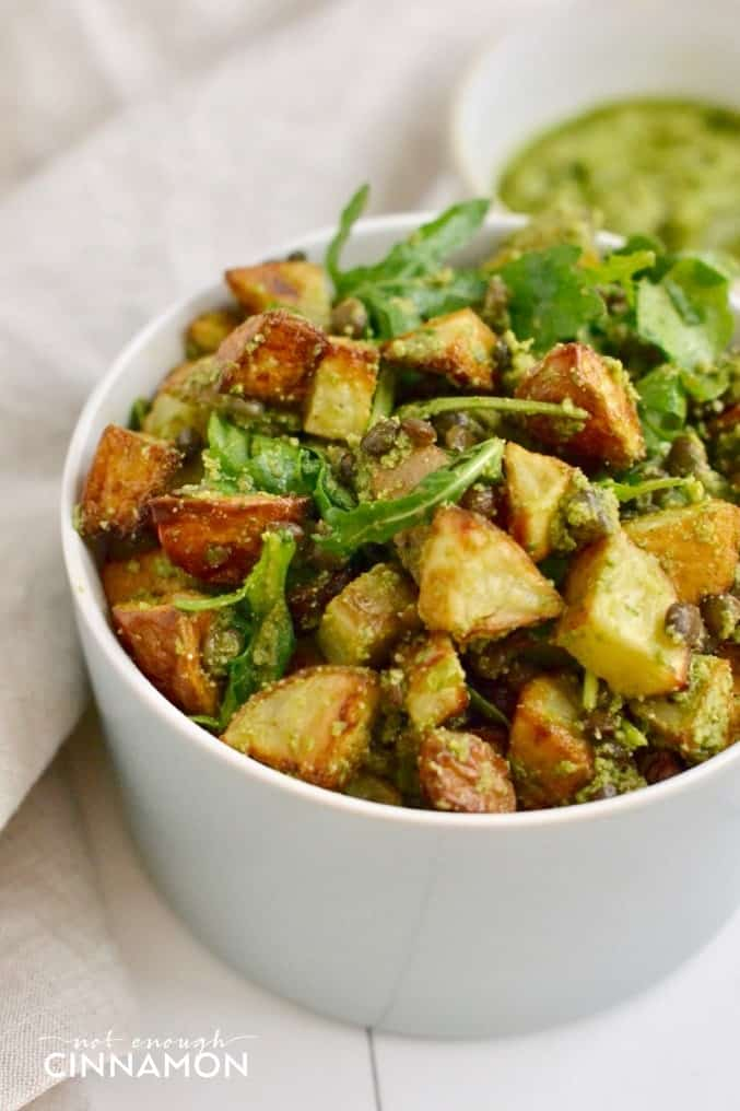 close-up of a bowl of roasted potato and lentil salad tossed with lemon walnut pesto dressing