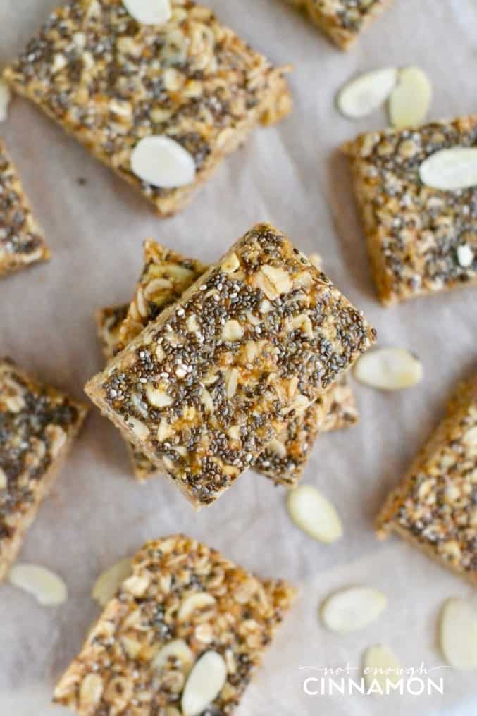 overhead shot of honey almond no-bake oatmeal bars with chia seeds on top arranged on a lined baking sheet
