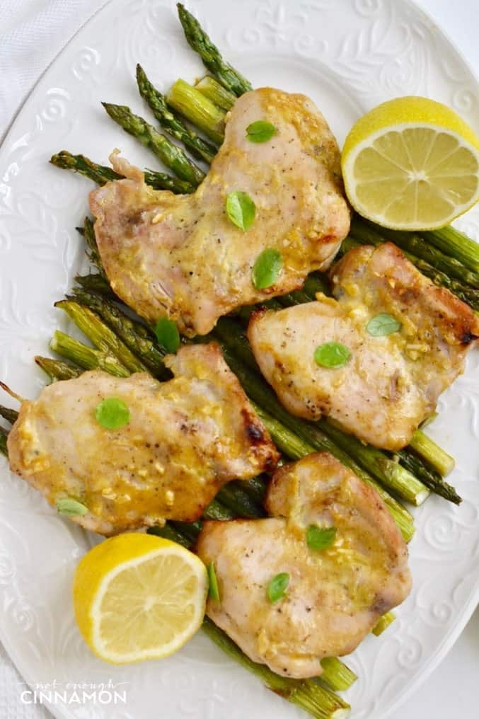overhead shot of a white platter of baked maple mustard chicken thighs on green asparagus