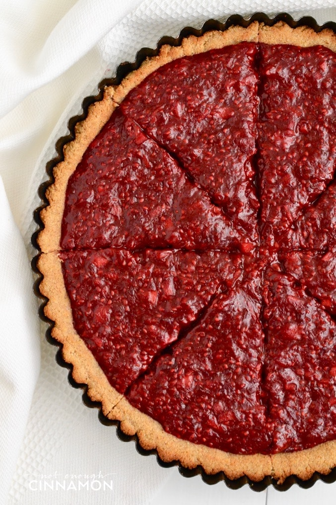 overhead shot of paleo raspberry tart with cinnamon-spiced coconut flour tart shell
