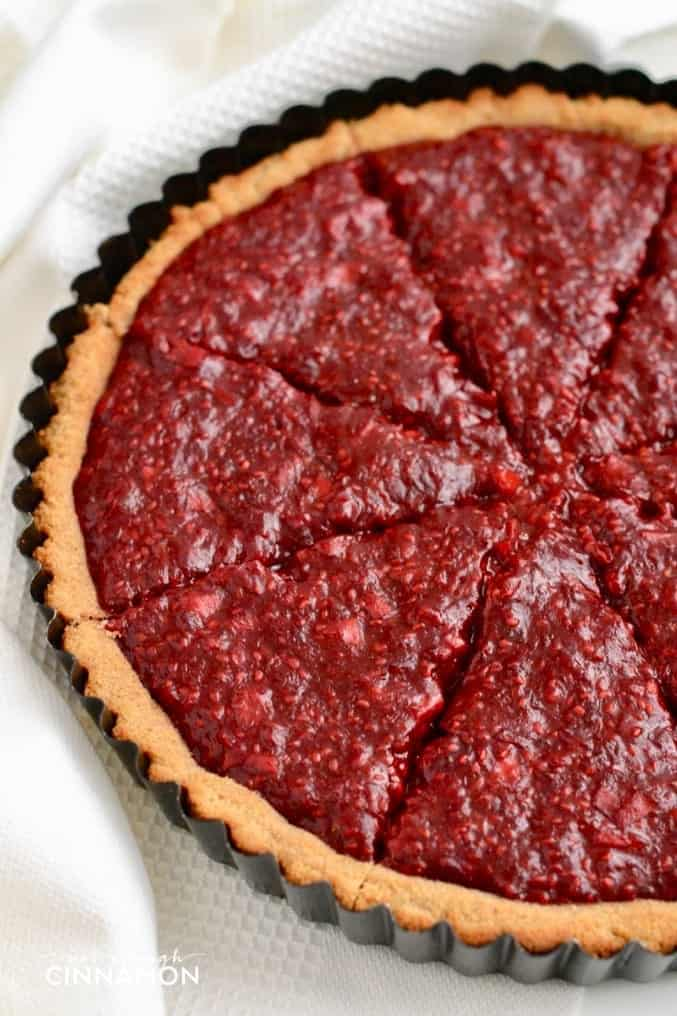 close-up of paleo cinnamon and raspberry tart with paleo coconut flour crust served in a metal tart baking dish