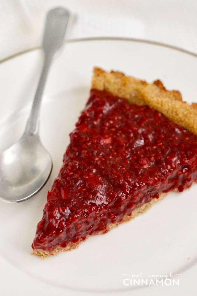 close-up of a slice of paleo raspberry cinnamon tart on a white plate with a spoon on the side