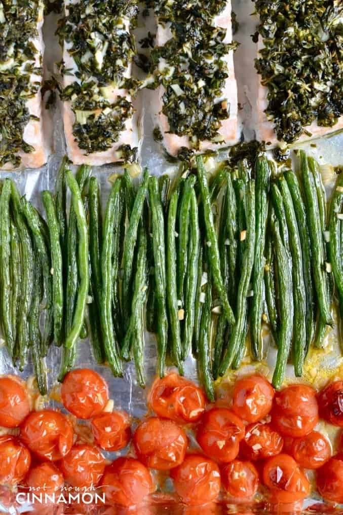 Paleo Sheet Pan Herbed Salmon arranged on a baking sheet with Green Beans and blistered Cherry Tomatoes