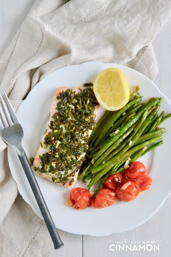 a serving of Paleo Sheet Pan Herbed Salmon served with Green Beans and Cherry Tomatoes on a white plate