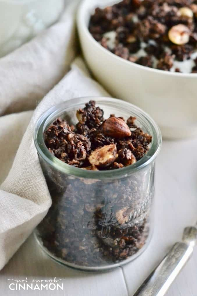 close-up of a small glass jar of homemade chocolate hazelnut granola