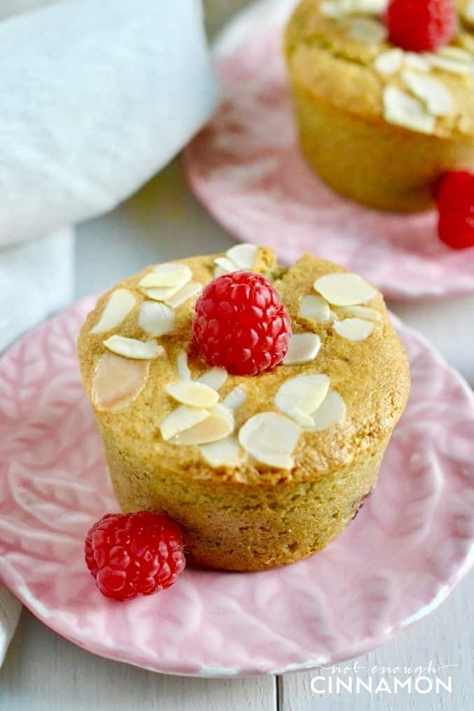 two healthy raspberry almond muffins on small pink plates topped with fresh raspberries