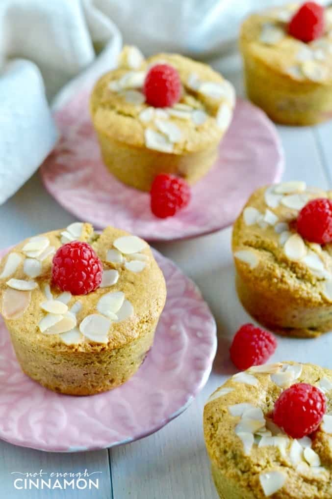 side view of raspberry almond flour muffins on pink plates topped with almonds and raspberries