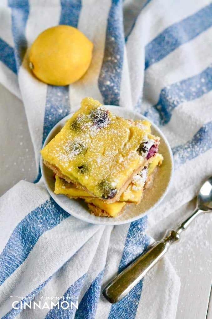 overhead shot of a plate of stacked Blueberry Lemon Bars dusted with icing sugar
