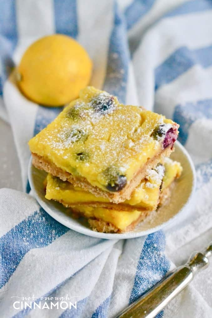 side view of a stack of healthy blueberry lemon bars on a small white plate with a lemon in the background