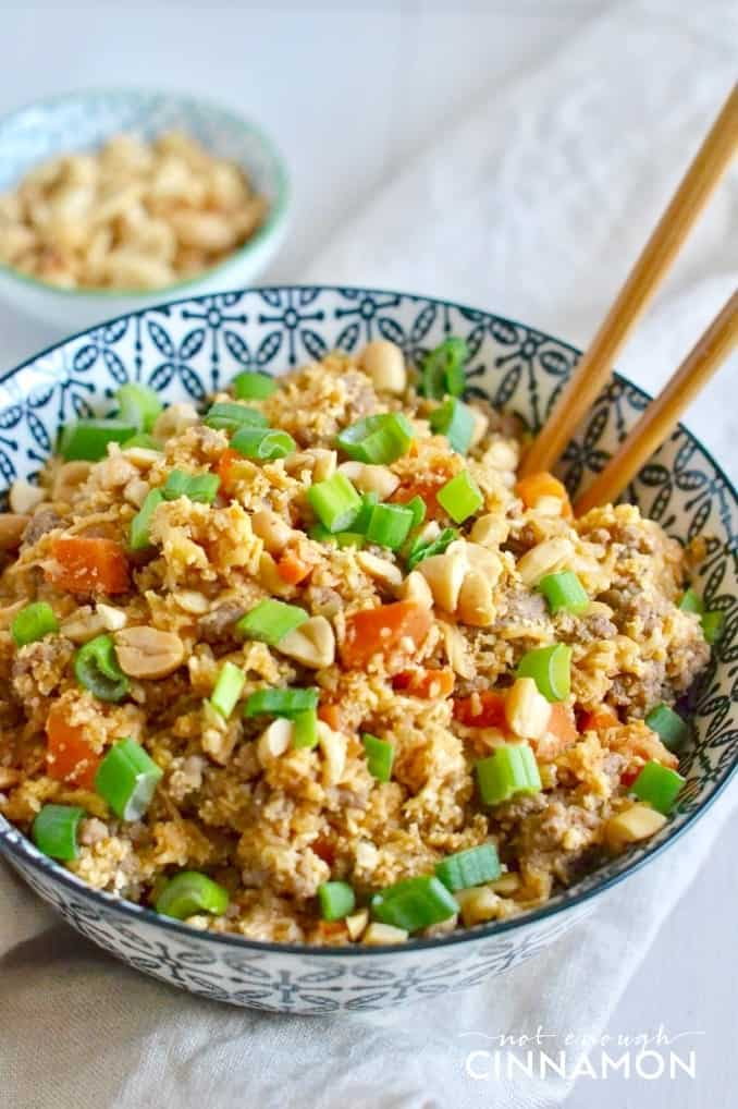 a bowl of low carb Asian cauliflower fried rice with chopsticks