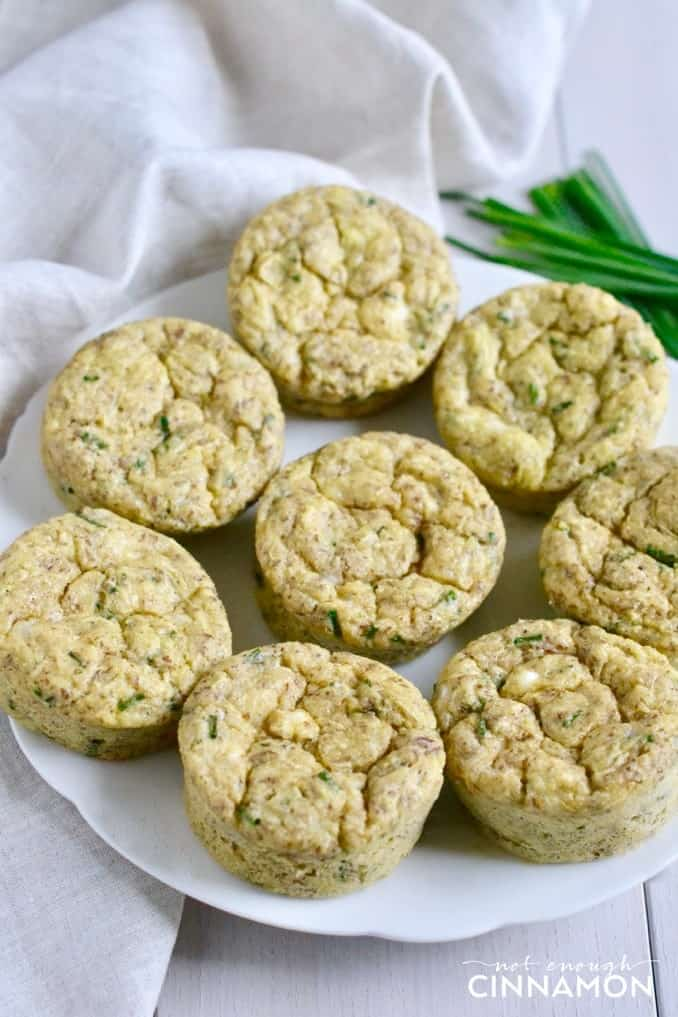 a plate of Gluten Free Zucchini Muffins with feta and chives on a white table
