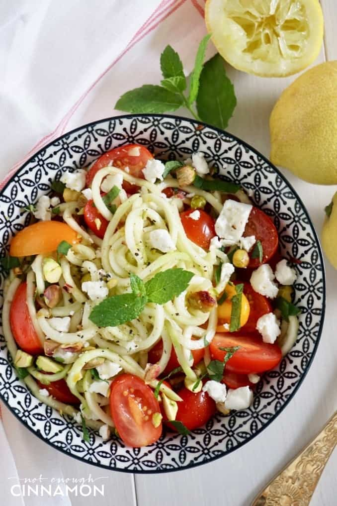 overhead shot of a bowl of low-carb zucchini noodle salad with pistachios, tomatoes and mint